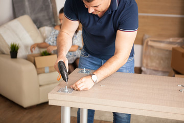 Man is working with furniture assembly using electric screwdriver in new house.Man using tools.