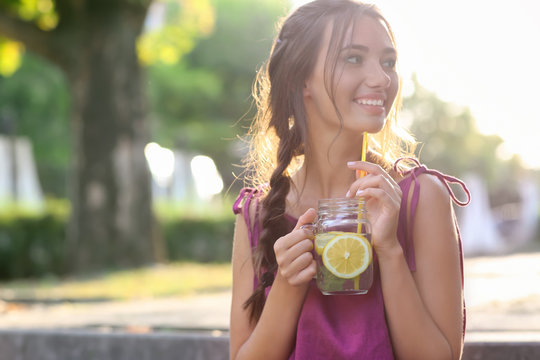 Young woman with mason jar of fresh lemonade outdoors