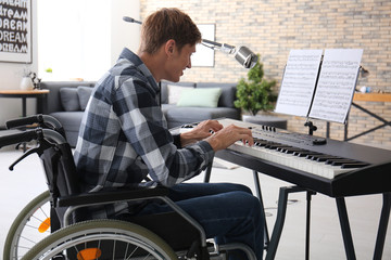 Young musician in wheelchair playing synthesizer at home