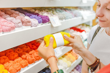 Woman choosing yarn and wool balls for purchase in craft shop
