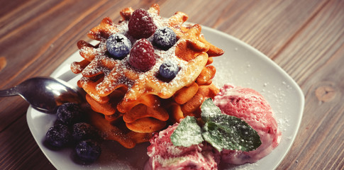 Plate of belgian waffles with ice cream and fresh berries - raspberries and blueberries.top view
