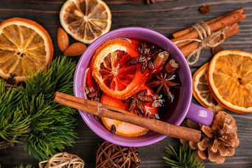 Cup of delicious mulled wine on wooden table
