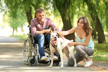 Young man in wheelchair with his wife and service dog outdoors