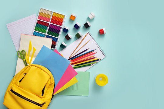 School stationary supplies sets and knapsack on blue background. Top view.