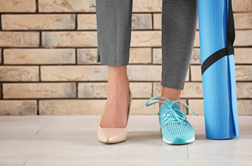 Young woman wearing high-heeled shoe and sneaker near brick wall. Concept of balance between rest...