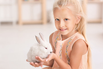Little girl with cute rabbit at home