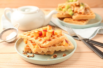 Delicious waffles with peach on plate