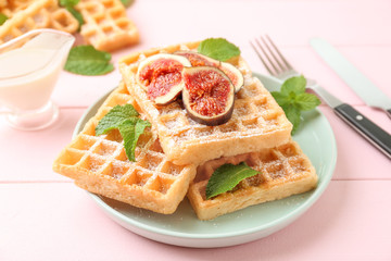 Delicious waffles with fig slices on plate