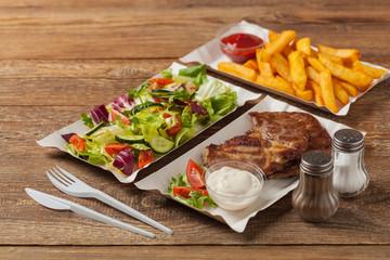 Grilled pork neck served on paper trays.