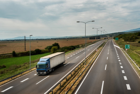 Blue lorry truck driving on asphalt highway road with High-mast lighting in a pastoral landscape