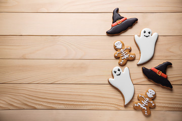 Creative cookies prepared for Halloween party on wooden background