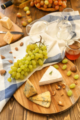 Wooden board with cheese and fresh ripe grapes on table