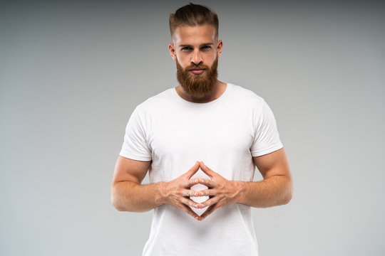 Barbershop advertising. Close up portrait of severe hot red bearded guy with stylish hairdo. He is standing with crossed arms on pure background, in casual light t shirt