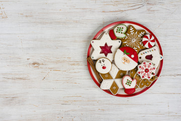 Plate with various colorful christmas gingerbread isolated on wooden background