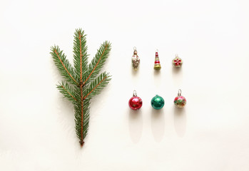 Christmas composition, minimalistic style with copy space. Fir branch and old shabby vintage decorations on white background. Flat lay, top view.