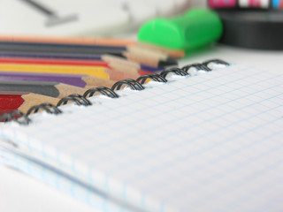 close-up of blurred image of checkered Notepad and pencils on white background