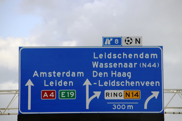 Directions signs above motorway A4 at a split at Prins Clausplein crossing with also route to regional road N14 in the Netherlands