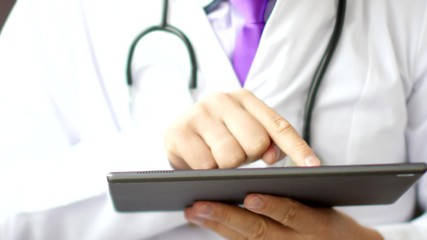Medical doctor using touchscreen digital tablet close-up