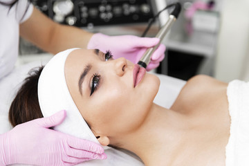 A woman came to laser hair removal facial. The woman lies and smiles, the doctor leads him in the face with a modern laser epilator. They are in the modern clinic.close up