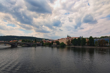 Scenic view of historical center of Prague, Manes Bridge and Vltava river at cloudy summer day. Buildings, cathedrals and landmarks of old town, Prague, Czech Republic