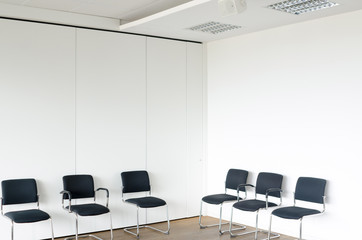 Chairs in waiting room white walls, corner view