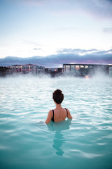 Foto auf Acrylglas Europäische Regionen Woman relaxes and enjoys of spa in hot spring Blue Lagoon in Ice
