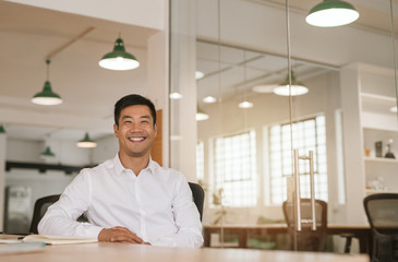 Successful Asian businessman smiling while sitting at his office desk Fototapete