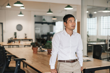 Young Asian businessman standing in an office deep in thought