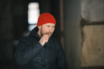 Vape in life. Young white man in red hat and black jacket is smoking an electronic cigarette in the corridor of a ruined house.