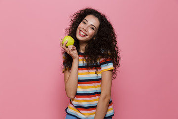 Photo of caucasian woman 20s with curly hair smiling and holding green apple, isolated over pink background