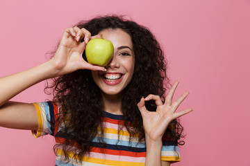 Photo of amusing woman 20s with curly hair smiling and holding green apple, isolated over pink background