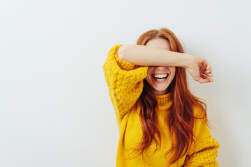 laughing woman covering her eyes with her arm