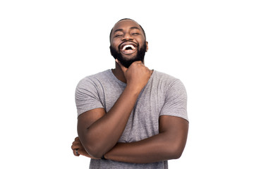 Friendly looking positive Afro American stylish man with hair style and bristle smiling broadly during nice conversation with good old friend, standing isolated at grey studio wall. Horizontal picture