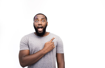 African American man grins at camera, indicates copy space for tex or logo, advertises something. Surprised man points with fore fiinger, shocked expression, isolated over white background. Look here!