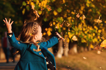 Happy little girl playing with autumn leaves. Cute child having fun in park. Stylish baby girl in blue coat throws autumn leaves outdoors. Happy childhood, season and people concept. Autumn fashion.