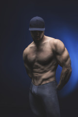 healthy muscular young man isolated on black background. Studio shot. Copy-space.