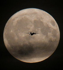A passenger plane is seen with the full moon behind as it begins its final landing approach to Heathrow Airport in London, Britain