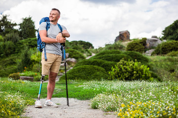 Cheerful man with prosthesis standing with Nordic walking sticks