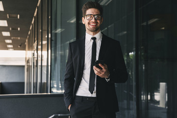 Portrait of attractive businessman dressed in formal suit standing outside glass building, and holding mobile phone