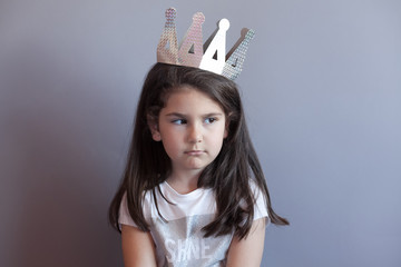 Pretty sad child girl with long brunette hair with crown on head isolated on grey background. Beautiful child true emotions. Place for text