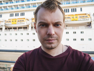 Young man makes selfie near a cruise ship.
