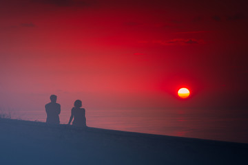 romantic scene with couple watching beautiful red sunset
