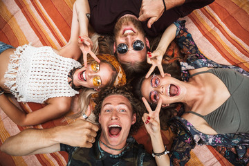 Photo of attractive hippies guys and girls laughing, and lying on blanket in circle outdoor