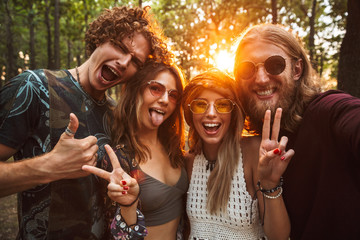 Photo of joyful hippie people men and women, smiling and taking selfie in forest