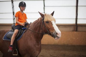 Boy in helmet learning Horseback Riding