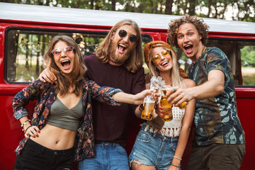 Group of lovely hippies men and women smiling, and drinking beer near vintage minivan into the nature