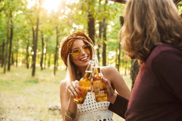Photo of happy couple hipsters man and woman laughing, and drinking beer in forest