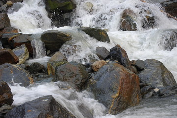 Stream of water in mountain river with stones close-up