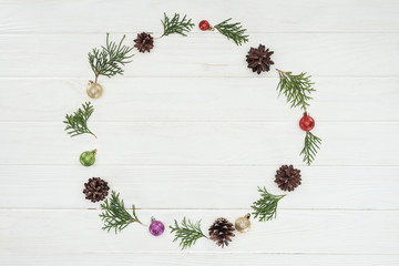 top view of evergreen coniferous twigs, pine cones and baubles on wooden background