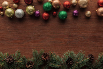 top view of shiny colorful baubles and coniferous twigs with pine cones on wooden background